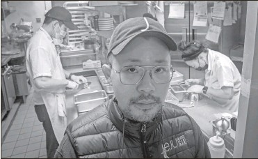 ?? Ap-bebeto Matthews ?? Korean American chef Douglas Kim, center, owner of the restaurant Jeju, which was vandalized during last year's racial injustice protests, is shown in the kitchen as food is being prepped, on Feb. 13 in New York. Asian Americans have been facing a dangerous climate since the coronavirus entered the U.S. a year ago. A rash of crimes victimizing elderly Asian Americans in the last two months has renewed outcry for more attention from politicians and the media.