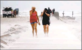 ?? Annie Rice Corpus Christi Caller-Times ?? PEOPLE SHIELD their faces from sand Monday on the Packery jetty in Corpus Christi, a day before the Nicholas storm weakened over southeastern Texas.