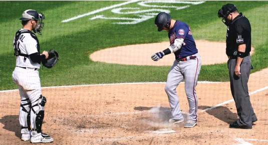 ?? AP ?? The Twins' Josh Donaldson kicks dirt on home plate after his home run in the sixth inning Thursday, prompting umpire Dan Bellino to eject him from the game.