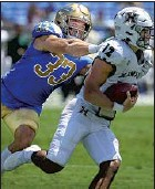 ?? Luis Sinco Los Angeles Times ?? THE BRUINS' Bo Calvert chases down Hawaii quarterback Chevan Cordeiro during UCLA's 44-10 victory Aug. 28.