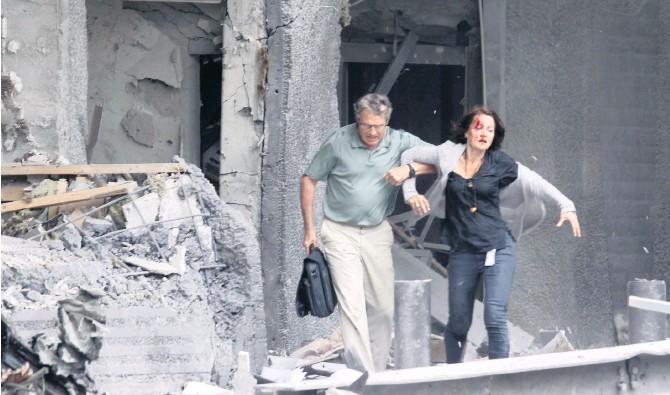 ?? Arkivbild: Morten Holm ?? En skadad kvinna får hjälp ut ur en byggnad av sin kollega i regeringskvarteret efter explosionen.