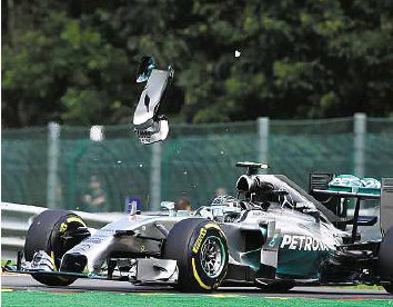 ??  ?? Error of judgement A piece of wing flies over Nico Rosberg's car after a collision with Mercedes teammate Lewis Hamilton at the Spa- Francorchamps circuit in Spa late lastmonth.AFP
