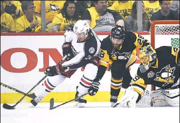 """?? Peter Diana/Post-Gazette ?? Penguins defenseman Ian Cole battles Blue Jackets winger Brandon Saad in Game 1. Making quick work of the Blue Jackets will allow the Penguins to rest, but """"we can't just take the next four days off,"""" Cole said."""