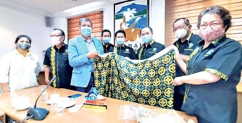 ??  ?? Joniston receiving a souvenir from the Kadazandusun Chamber of Commerce and Industry (KCCI) delegation led by Bonipasius during the courtesy call on Wednesday.