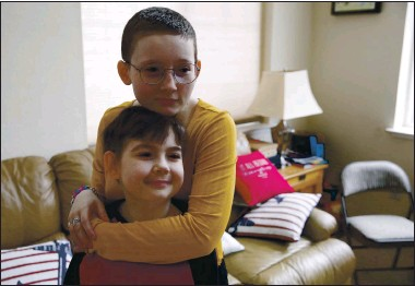 ?? PHOTOS BY JANE TYSKA — STAFF PHOTOGRAPHER ?? Matthew Ouimet, 10, and his sister, Molly, 18, wait at their home to meet their new companion dog, a black Lab named Winnie. Matthew and Molly, two immunocompromised children with the same rare genetic disease, are preparing for kidney transplants.