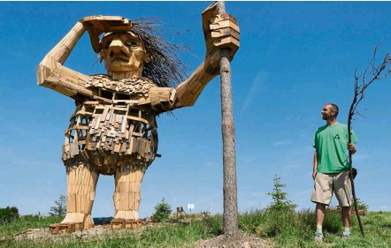 ?? — Photos: TNS ?? Danish artist Thomas Dambo stands beside his creation, Joe the Guardian, one of the six larger-than-life-trolls in Morton Arboretum in Lisle, Illinois, the United States, overlooking Highway 53. Dambo and his team created the trolls using hundreds of...