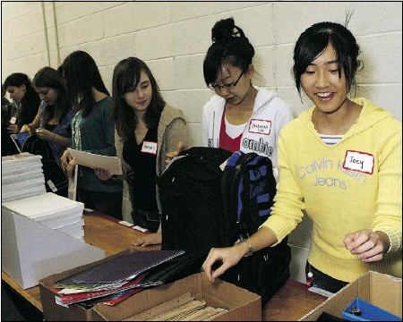 ?? Lorraine Hjalte, Calgary Herald ?? Joey Poon, right, among nearly 100 volunteers, including members of the Calgary Roughnecks and students from Western Canada Interact Club, help Na'amat Canada Calgary fill backpacks with pencils, paper, scissors and other school supplies.