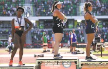 ?? Patrick Smith / Getty Images ?? U.S. hammer thrower Gwen Berry (left) turns from the flag and national anthem after her thirdplace finish Saturday.
