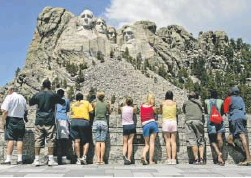 ?? Charlie Riedel, AP file photo ?? Visitors watch while workers pressure wash the granite faces at Mount Rushmore National Memorial in South Dakota.