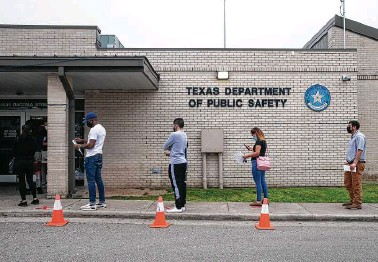 ?? Yi-Chin Lee / Staff photographer ?? Socially distanced Texans wait in line Thursday for their appointment at the DPS driver's license office on Dacoma.