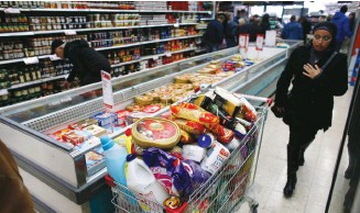 ?? (Ronen Zvulun/Reuters) ?? An overflowing grocery cart in a Jerusalem supermarket. Shouls unhealthy products be labeled?