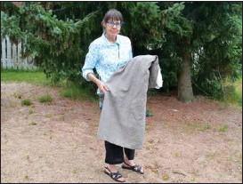 ??  ?? ARKEOLOG. Jaana Riikonen har deltagit i utgrävningarna vid Kyrkbacka i Ravattula. Hon håller en rekonstruerad klänning i sin famn.
