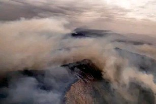 ?? (AP) ?? Smoke fi ll ed mountains near the town of Jubrique, in Mal aga province