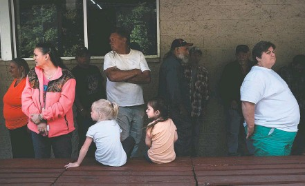 ?? SPENCER PLATT/GETTY IMAGES ?? In Welch, W.Va., residents wait in line — some overnight — for free groceries at the Five Loaves and Two Fishes Food Bank.