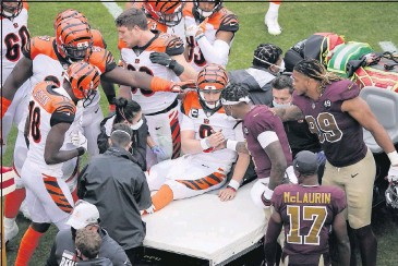 ?? THE ASSOCIATED PRESS ?? Cincinnati quarterback Joe Burrow(9) shakes hands withWashington quarterbackDwayne Haskins as Burrows is carted off the fieldwith a knee injury in the second half of the Bengals' road loss Sunday.