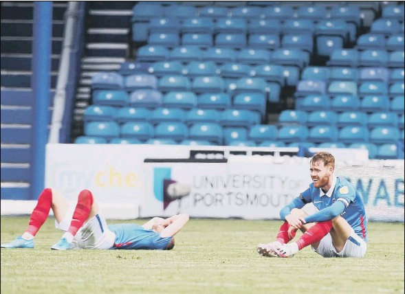?? Picture: Joe Pepler ?? DREAM IS OVER A dejected Jack Whatmough and Tom Naylor after Pompey choked on the final day to miss out on the play-offs