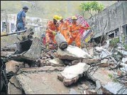 ?? SUSHIL KUMAR/HT PHOTO ?? Rescue workers clear debris of the collapsed building in east Delhi's Laxmi Nagar area on Sunday.