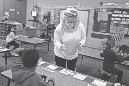 ?? CHRISTINE T. NGUYEN/AP ?? Kindergarten teacher Sherri Shober doles out hand sanitizer to students Jan. 19 in Brooklyn Park, Minn. Parents skeptical of the safety of in-person learning are one of several obstacles for the summer school effort.
