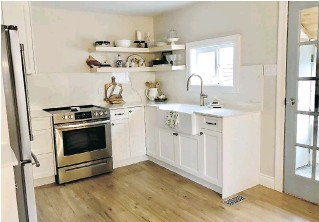 ??  ?? Porcelain tiles that resemble marble were used on the countertop and backsplash. The homeowners installed floating wood shelves over one corner of the kitchen countertop and styled it with items reminiscent of their Italian heritage.
