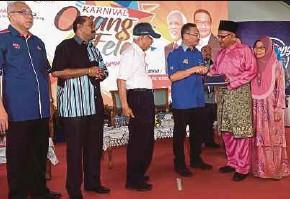 ?? BERNAMA PIC ?? Defence Minister Datuk Seri Hishammuddin Hussein handing over land grants to Husin Ismail and his wife, Saniah Saleh, in Felda Ulu Belitong, Kluang, Johor, yesterday. Looking on is Tan Sri Shahrir Abdul Samad (third from left).