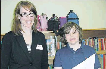 ?? - Sylvia Jacquard photo ?? Booker School student Alden Mulherin and his teacher Christie Dyer discuss the letters he wrote to his municipal councillor and to the Port Williams and District Lions Club about traffic on Belcher Street. Mulherin and Dyer were among the school's staff and students welcoming the public to school's new home in Port Williams at their open house on April 8.