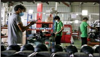 ?? Photo: EPA-EFE ?? Myanmar workers wear face masks on a car assembly line in motor plant in Yangon in May.