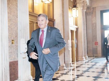 ?? J.SCOTTAPPLEWHITE/AP ?? Sen.Joe Manchin, D-W.Va., rushes into the Senate last month ahead of an annoucement by Mitch McConnell.