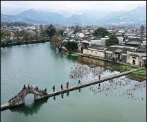 ?? SHI YALEI / XINHUA ?? Tourists cross a bridge in Hongcun Ancient Village, Yixian county, Anhui province.