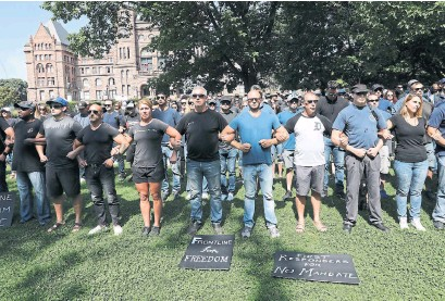 ?? RICHARD LAUTENS TORONTO STAR ?? Demonstrators gather for a silent vigil at Queen's Park Monday as part of a series of anti-vaccination protests held across Canada. Dozens of protesters also converged on Toronto's Hospital Row, chastising health-care workers who arrived to counter-protest.