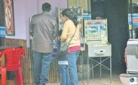 ??  ?? Una familia prueba suerte con una de las tragamonedas que está en un copetín. El uso de esas máquinas está prohibido a menores.