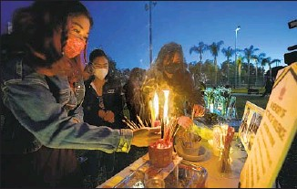 ?? Damian Dovarganes Associated Press ?? AT A MONTEREY PARK candlelight vigil, women pay their respects to victims of the spa shootings in Georgia. Like any public health crisis, there is no quick fix for the gun violence epidemic.