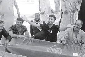 ?? ANMAR KHALIL/AP ?? Prayers and anger in Iraq: Mourners bury loved ones Tuesday in Najaf after a fire swept through a COVID-19 ward Monday at al-Hussein Teaching Hospital in the southern city of Nasiryah. The death toll rose to 92 as relatives lashed out at the government. In April, at least 82 people, many coronavirus patients or their relatives, died in a fire at a hospital in Baghdad.
