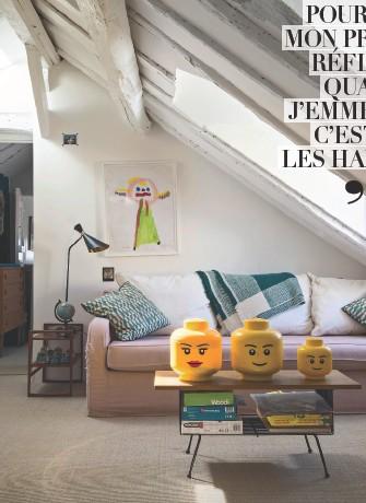 """??  ?? Plébiscité par les enfants, le petit salon est devenu leur pièce préférée pour jouer, comme en témoignent les personnages Lego posés sur la table basse, chinée en Belgique. Lampe vintage. Canapé """"Luna"""", coussins et plaid, Maison Sarah Lavoine. Au mur, un dessin de Roman."""