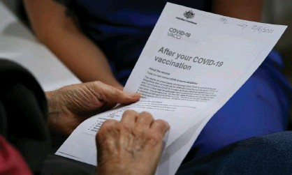 ?? Photograph: Lisa Maree Williams/Getty Images ?? A patient looks at an information pack ahead of receiving the Covid-19 AstraZeneca vaccine at a GP in Sydney. Overnight the EU drug regulator said that rare blood clots would be listed formally as a side-effect of the AstraZeneca jab.