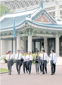 ?? KIM JOO HYUNG/YONHAP VIA REUTERS ?? New president Moon Jae-in talks with senior presidential secretaries as they take a walk at the Blue House in Seoul yesterday.