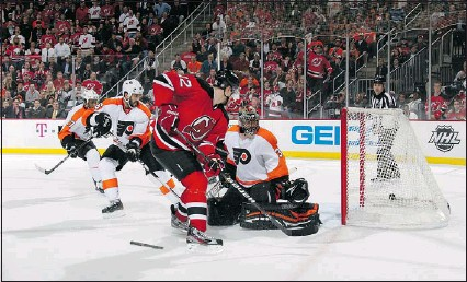 ?? — GETTY IMAGES ?? Alexei Ponikarovsky (12) of the New Jersey Devils scores the game-winning goal in overtime to defeat the Philadelphia Flyers in Game 3 of their Eastern Conference semifinal series Thursday.