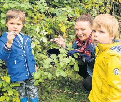 ??  ?? Berry interesting Cohen Baird examines a bramble with mum Natalie and brother Kasper