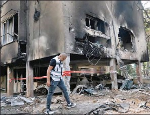 ?? (AFP) ?? An Israeli man checks the damages in a residential building after a rocket attack from the Gaza Strip, in the central Israeli city of Petah Tikva, on Thursday.