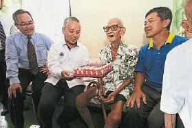 ??  ?? ↑曼銳區州議員莫哈末西亞(左二起)獻上蛋糕提前為邱文秀祝壽。左一是霹靂州移民局長祖拉茲蘭,右一是瓜拉光新村村長邱穆財。