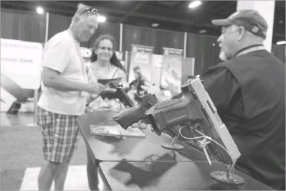 ?? File Photo/staff ?? A 2019 NRA Personal Protection Expo at the Tarrant County Convention Center in Fort Worth drew a crowd of gun enthusiasts. A divisive measure that would allow people to carry handguns in public without a license will need a final sign-off in the House before it can move to the Senate, where its fate is unclear. The Texas State Rifle Association celebrated Thursday's vote.