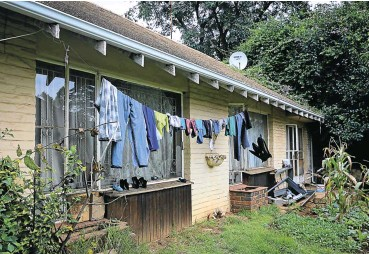 ?? Pictures: Sebabatso Mosamo ?? Laundry dries on a line strung under the eaves of the once-smart house in Hurlingham, Sandton. More than 20 people appear to be living on the property, which has broken windows and at least one nonfunctioning toilet.