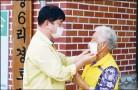 ??  ?? 최문순 화천군수가 노인 일자리 운영상황 점검 현장에서한어르신의마스크착용을도와주고 있다.