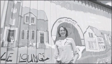 ??  ?? Youth Centre coordinato­r Clea Corman standing beside representa­tion of Le Lounge, part of the 150-foot mural painted by Trevor Mckinven. Corman is also operations manager of the Phelps Helps tutoring program which is seen to her left.