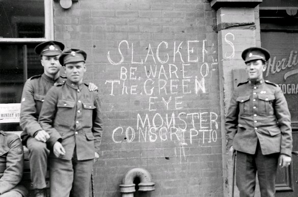 ??  ?? A group of wounded soldiers stands in front of graffiti condemning able-bodied men who had not enlisted to serve in the war, circa 1917–18.