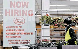 ?? NAM Y. HUH/AP ?? A man pushes carts by a hiring sign at a Jewel Osco grocery store in April in Deerfield, Ill.