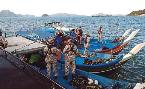 ??  ?? ANGGOTA APMM Kedah dan Perlis melakukan pemeriksaan ke atas bot nelayan di kawasan perairan pulau, semalam.