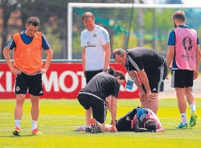 ??  ?? Michael O'Neill checks on Kyle Lafferty as he lies injured during training at Parc de Montchervet.