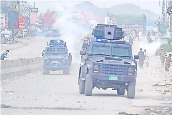 ?? — AFP file photo ?? Supporters of Tehreek-e-Labbaik Pakistan (TLP) party throw stones over the police armoured vehicle during a protest in Barakahu neighbourhood of Islamabad.