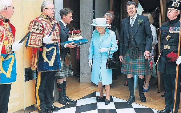 ?? ANDREW MILLIGAN / AFP ?? Isabel II inspecciona la corona en el Black and White Corridor después de la apertura de la sesión del Parlamento escocés ayer en Edimburgo