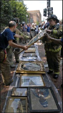 ?? BY STEPHEN J. BOITANO — ASSOCIATED PRESS ?? Firefighters salvage artwork from Georgetown Neighborhood Library. The mayor's budget includes funding for rebuilding the library and Eastern Market.